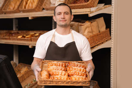 Portrait of professional baker holding tray with fresh buns near showcase in store 版權商用圖片