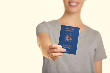Woman holding Ukrainian travel passport against blurred background, closeup with space for text. International relationships Stock Photo