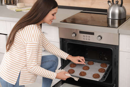 Beautiful woman taking out tray of baked cookies from oven in kitchen Stock Photo