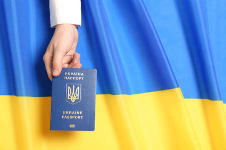 Woman holding Ukrainian travel passport over national flag, top view with space for text. International relationships