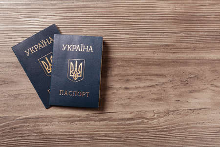 Ukrainian internal passports on wooden background, top view. Space for text