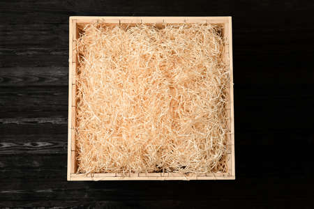 Wooden crate with filler on dark background, top view