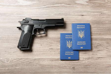 Gun with Ukrainian travel passports on wooden background, flat lay Stock Photo
