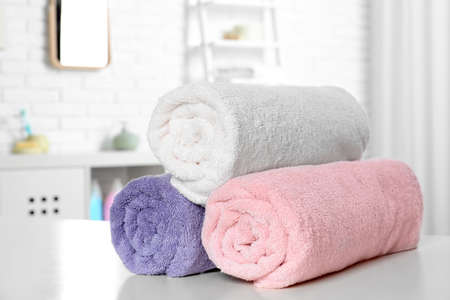 Rolled fresh towels on table in bathroom