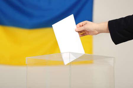 Woman putting voting paper into ballot box against Ukrainian flag, closeup