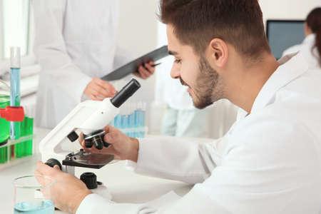 Medizinstudent, der mit Mikroskop im modernen wissenschaftlichen Labor arbeitet
