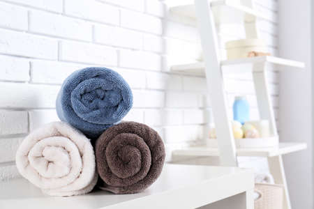 Rolled fresh towels on table in bathroom. Space for text Stock Photo