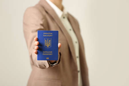Woman holding Ukrainian travel passport on light background, closeup with space for text. International relationships