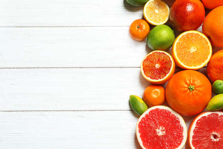 Flat lay composition with different citrus fruits and space for text on white wooden background Stock Photo