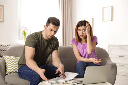 Sad couple counting money in living room Standard-Bild