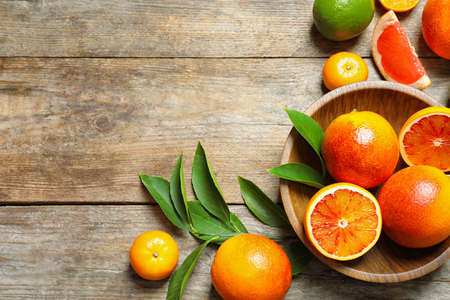 Flat lay composition with different citrus fruits and space for text on wooden background