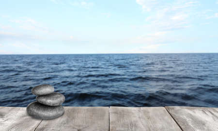 Stacked zen stones on wooden pier against sea, space for text Stock Photo