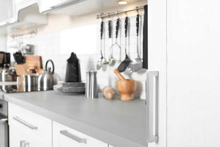 Blurred view of different appliances, clean dishes and utensils on kitchen counter