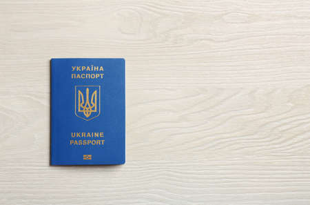 Ukrainian travel passport on wooden background, top view with space for text. International relationships