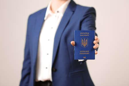 Woman holding Ukrainian travel passport on light background, closeup. International relationships