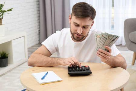 Happy young man with money at home