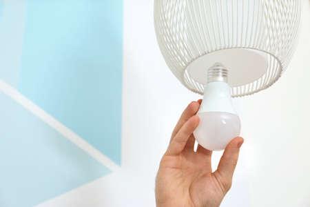 Hombre cambiando la bombilla de luz en la lámpara contra la pared de color, primer plano. Espacio para texto