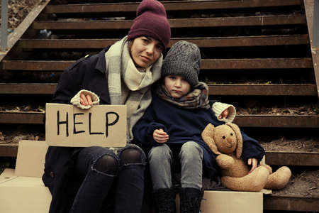 Poor mother and daughter with HELP sign sitting on stairs outdoors Banque d'images