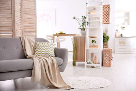Modern eco style living room interior with wooden crates, shelves and sofa Archivio Fotografico