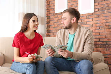 Beautiful young couple with money at home