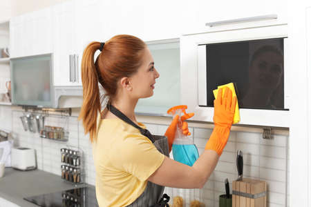 Woman cleaning microwave oven with rag and detergent in kitchen Archivio Fotografico