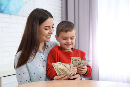 Happy mother and son with money at home