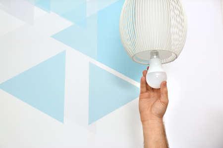 Hombre cambiando la bombilla de luz en la lámpara contra la pared de color, primer plano. Espacio para texto Foto de archivo