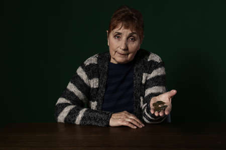 Poor senior woman with coins at table against color background
