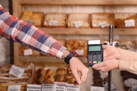Man using terminal for contactless payment with smart watch in bakery, closeup