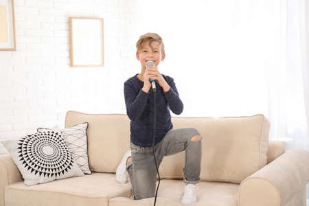 Cute boy with microphone on sofa in living room