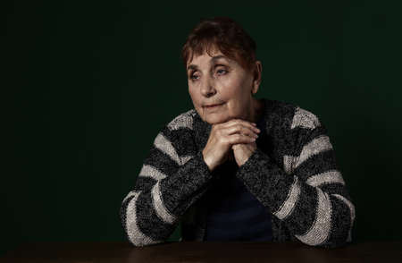 Poor senior woman sitting at table against color background. Space for text