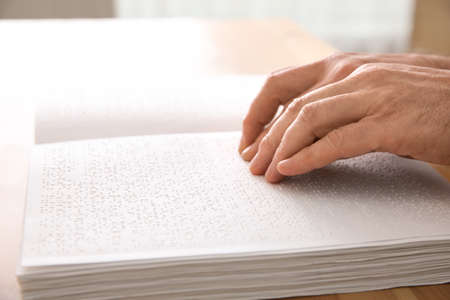 Blind man reading book written in Braille at table, closeup