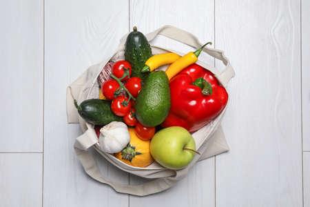 Bag full of fresh vegetables and fruits on light background, top view Reklamní fotografie