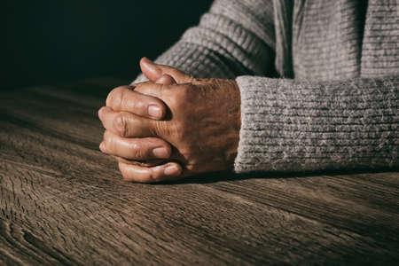 Poor senior woman at table, closeup of hands