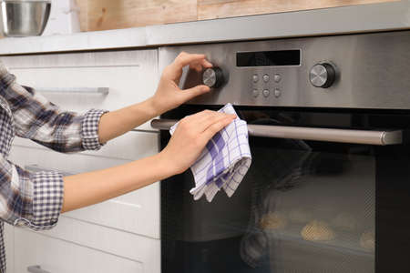 Young woman adjusting oven settings in kitchen, closeup Imagens
