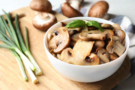 Delicious cooked mushrooms with basil in bowl on table
