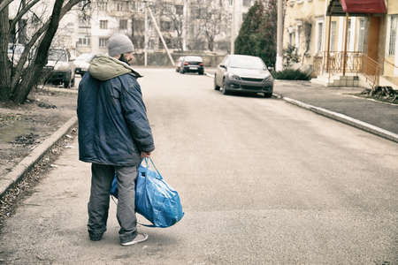 Poor homeless man with bag on city street Stock Photo