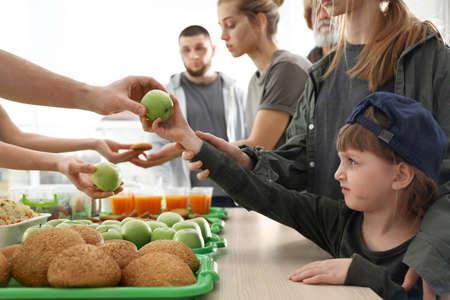 Volunteer giving apple to poor girl indoors Stock Photo