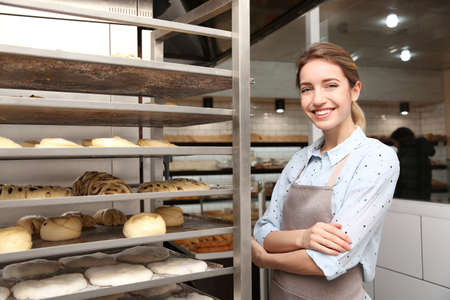 Baker at rack with pastries in workshop