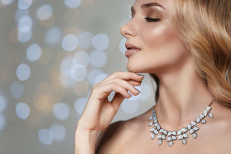 Beautiful young woman with elegant jewelry against defocused lights, closeup. Space for text