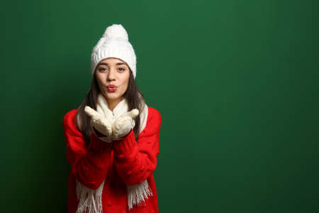Young woman wearing warm clothes on color background, space for text. Winter season Stock Photo