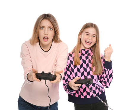 Young woman and teenage girl playing video games with controllers isolated on white