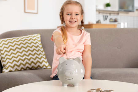 Cute girl putting coin into piggy bank at table in living room. Saving money Standard-Bild
