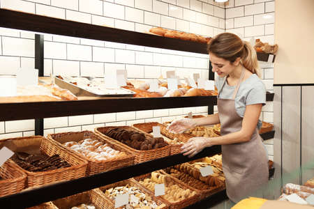 Beautiful woman near showcase with pastries in bakery shop Imagens