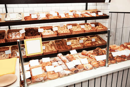 Showcase with different pastries in bakery shop Banco de Imagens