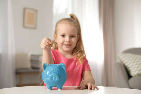 Cute girl putting coin into piggy bank at table in living room. Saving money Stock Photo