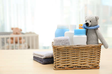 Wicker basket with baby cosmetic products, toy and towels on table indoors. Space for text