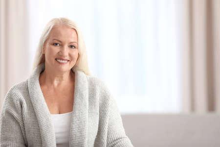 Porträt der schönen älteren Frau gegen unscharfen Hintergrund mit Raum für Text Standard-Bild