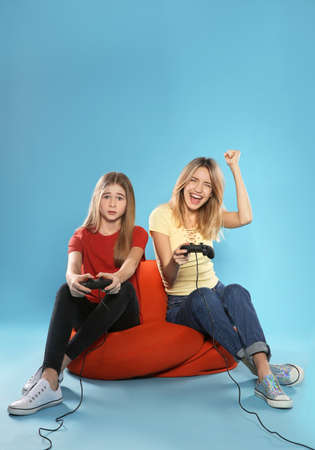 Young woman and teenage girl playing video games with controllers on color background. Space for text