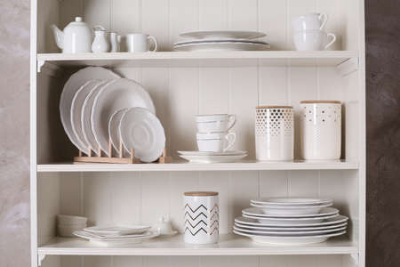 Stylish storage stand with different ceramic dishware at home Stockfoto